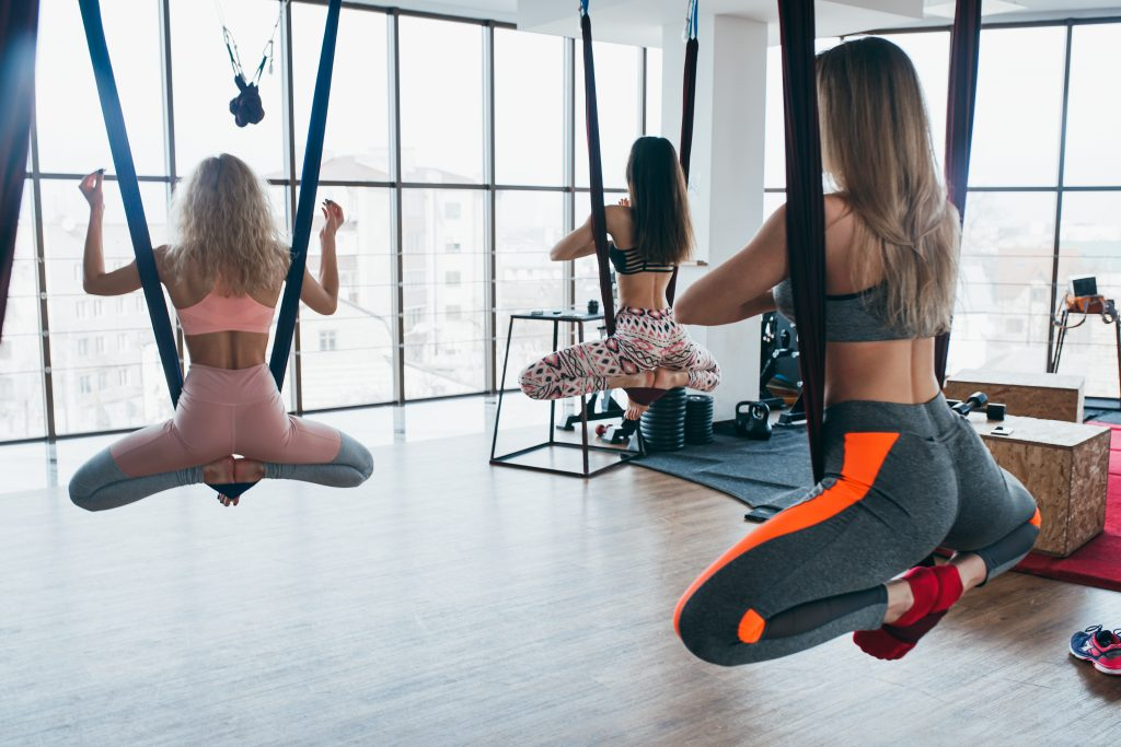 Young, beautiful, athletic girls do aerial yoga in the gym