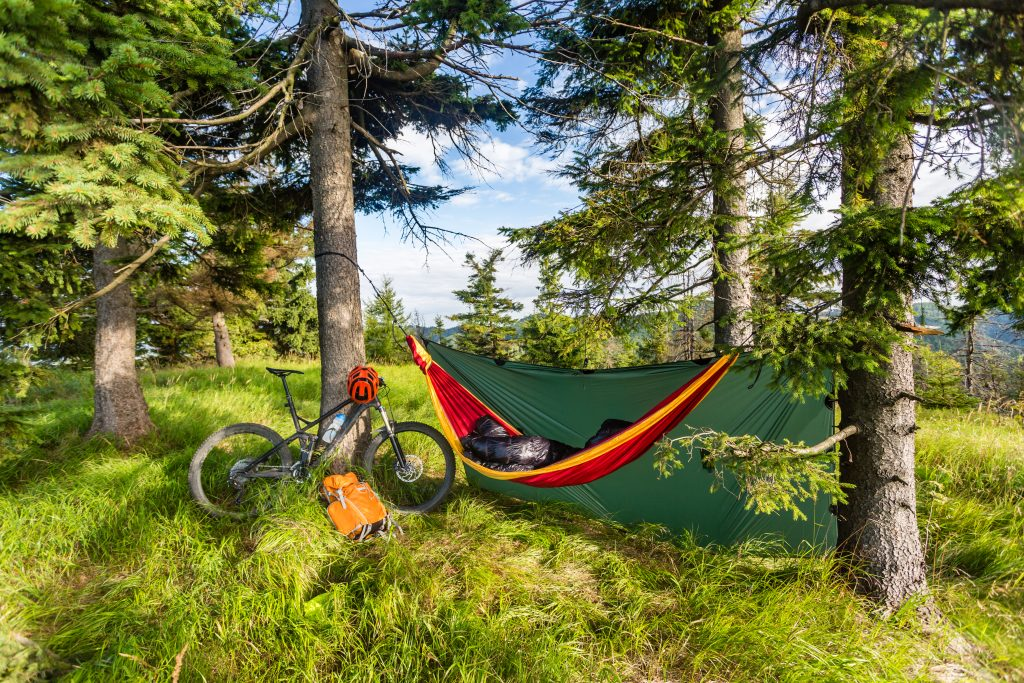 Camping in woods with hammock and sleeping bag on mountain biking adventure trip in green mountains.