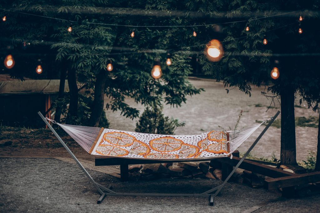 colorful stylish travel hammock with stand under lamp lights in summer for