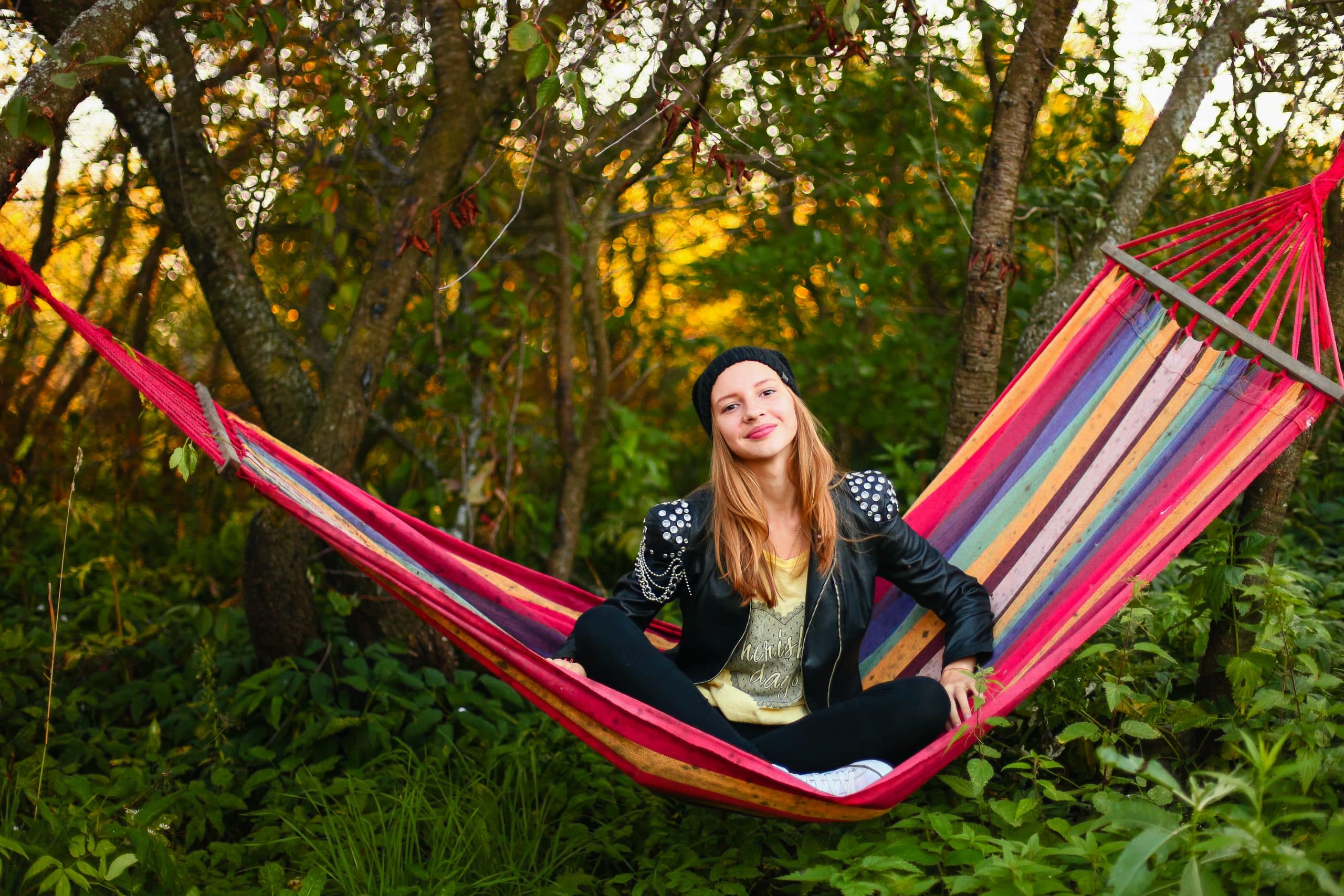 Happy Teengae girl sitting on a hammock