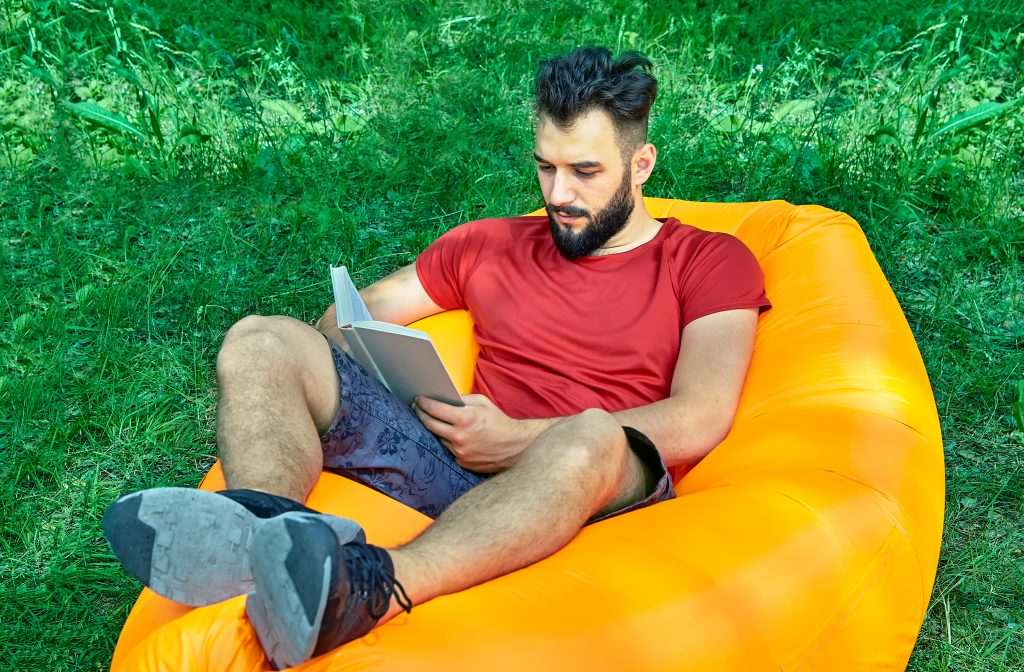Young attractive bearded student is relaxing with book in his hands on inflatable lounger during his holiday in forest.
