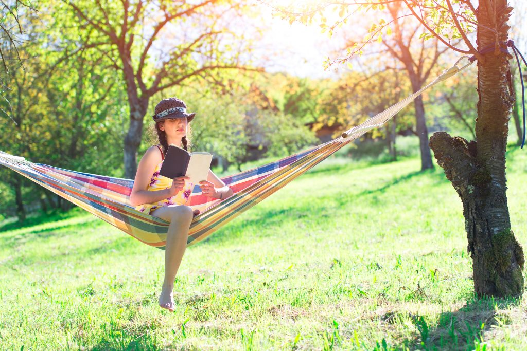 Woman reads sitting on a hammock
