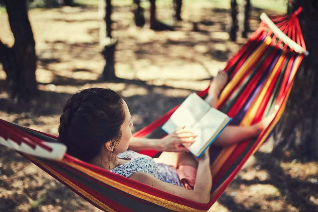 Woman resting on a hammock reading a book
