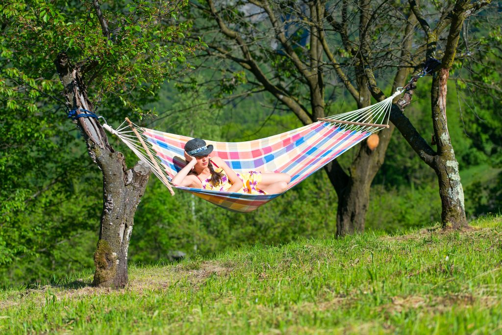 Woman resting on a hammock in the middle of a meadow in spring